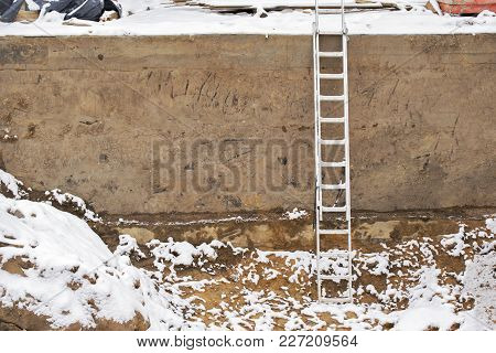 Empty Construction Pit And Ladder In Winter