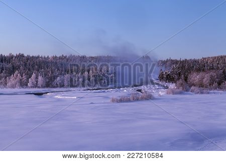 Cold Morning Mist Above The Rapids. Snow And Forests Up North.