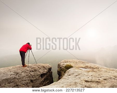 Professional Photographer Shooting. Artist Stay  With Tripod On Summit And  Takes Pictures Of Autumn