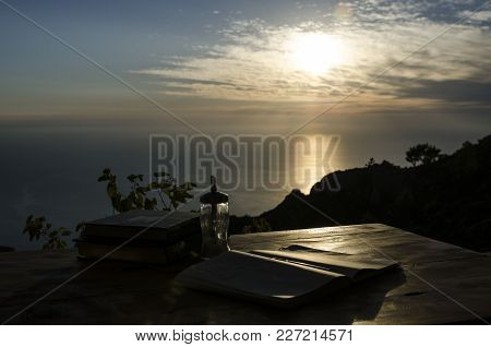 A Photograph In A Backlight, In The Foreground The Table On Which Lies A Book In The Rays Of The Set