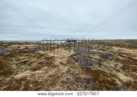 Dark House On The Rocky Field Covered By Faded Grass And Moss On The Background Of The Sea And The C