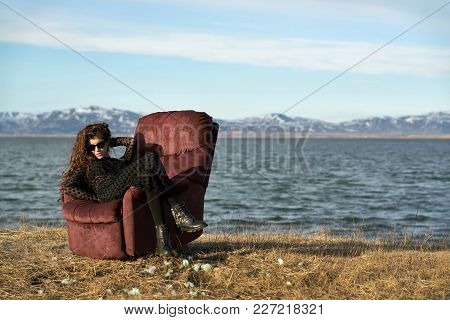 Delightful Girl In Sunglasses Sits On The Red Armchair On The Faded Grass Field On The Background Of