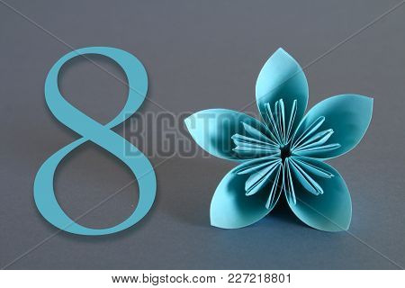 Paper Flower From Origami With The Number Eight On A Gray Background. March 8, International Women's