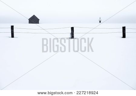 A Fence With Barb Wire, A Barn And A Column Shrine Are The Only Things To See In A Snowstorm