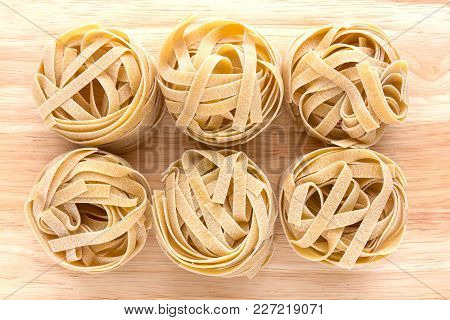 Macaroni Nests Close-up On A Wooden Surface. Tagliatelle Macaroni Lie A Bunch Next To Each Other.