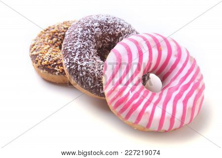 Assorted Doughnuts In The Glaze, Colorful Sprinkles And Nuts On A White Background