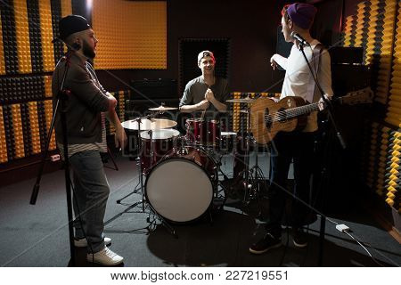 Band Of Young Musicians Having Discussion While Performing In Dim Recording Studio Making New Album