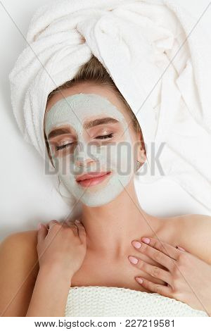 Portrait Of Beauty Woman Laying With Towel On The Head, Facial Mask, Making Massage. Spa Therapy. Re
