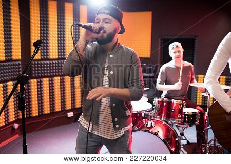 Portrait Of Modern Hip-hop Singer Performing With His Band In Recording Studio While Making New Albu