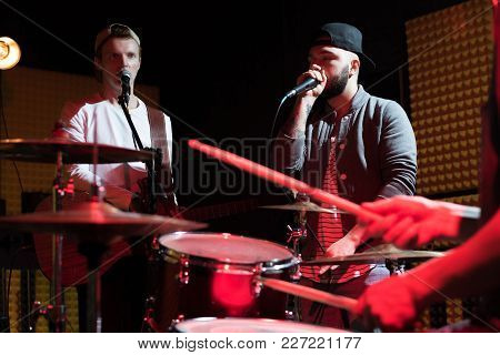 Portrait Of Hip-hop Singer Performing With His Band In Recording Studio, Drum Set In Foreground, Sce