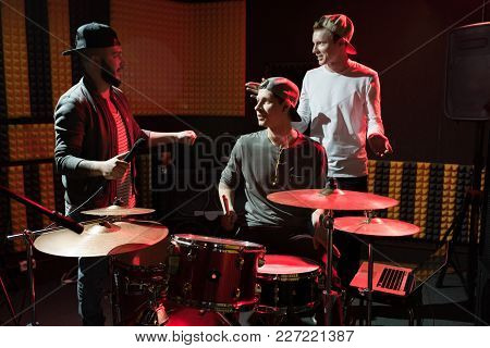 Portrait Of Modern Hip-hop Band Rehearsing In Recording Studio Lit By Red Lights While Making New Al