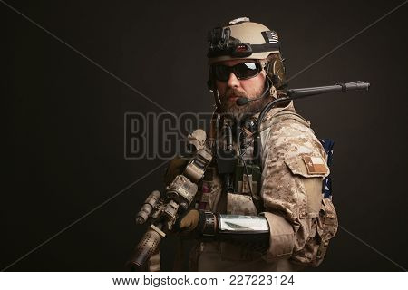 Brutal Man In The Military Desert Uniform And Body Armor Stands In A Fighting Rack And Holds His Rif