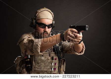 Brutal Man In The Military Desert Uniform And Body Armor Standing In A Fighting Rack And Aiming From