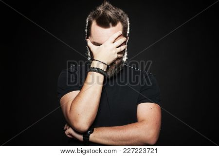 The Man Put His Hand To His Face In Studio On A Black Background. He's Very Unhappy And Sad. Body La