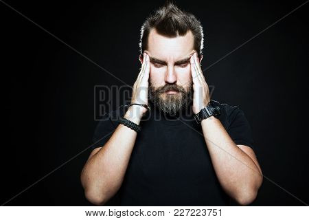 Terrible Headache. Frustrated Man Touching Head With Hands And Making Face While Standing Against Bl