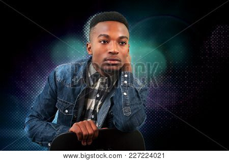 Young Man Sitting On A Chair Wearing Jeans Jacket Special Effects Blue Light Background