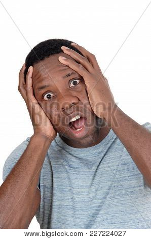 A Young African American Man Looking Horrified And Scary With His Hands On His Head And Big Eyes, Is