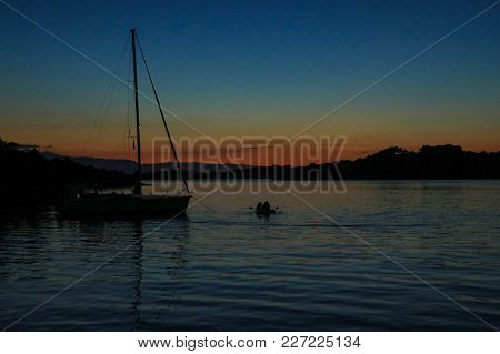 Late Evening Sunset Sailboat Anchoring In A Bay Near Porto Heli, Peloponnese, Greece. Horizontal.