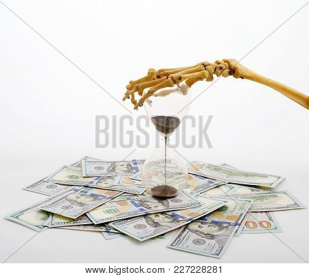 Skeleton Fingers Holding The Top Of Sand-glass Placed On Dollars. Time Is Running. Concept Of Time -
