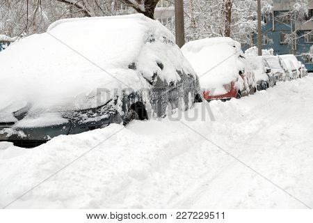 Snow-covered Cars Lined Up In The Street Of The City In Winter Day