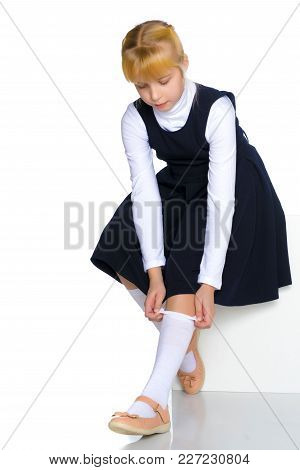A Nice Little Girl Straightening Her Knee Socks. The Concept Of A Happy Childhood, Beauty And Fashio