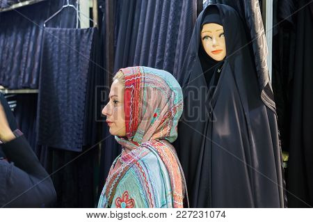 Tehran, Iran - April 29, 2017: One Woman In A Colored Hijab, Stands In The Profile Near The Store Wi