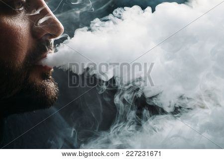Man Vaping E-cigarette With E-liquid, Close-up, Breathes Out Large Cloud Of Steam Or Vapor. Vape Con