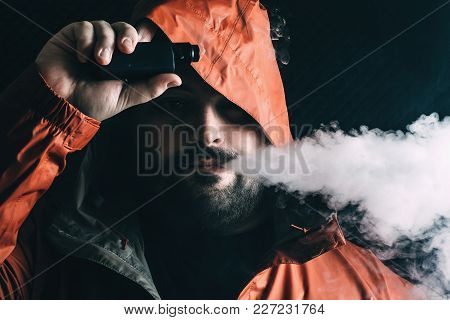 Man Smoker Vaping E-cigarette With E-liquid From Vape Rda Device, Breathes Out Vapor And Looks At Ca