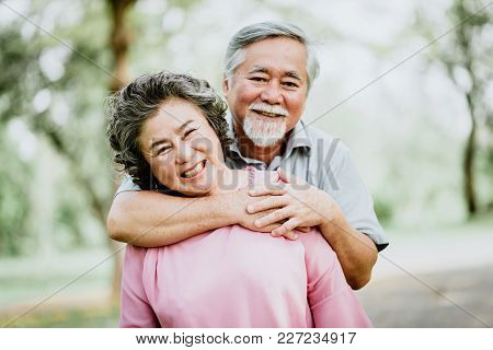 Happy Smile Senior Asian Couple Enjoying Quality Time At The Park. A Man Embracing Woman Closely. Su