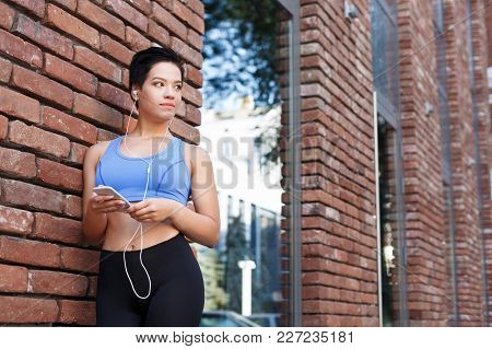 Woman Choose Music To Listen In Her Mobile Phone During Jogging In City, Having Rest, Looking Away,
