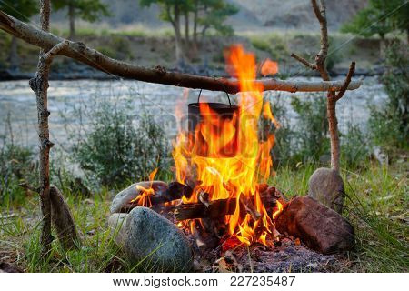 Cooking meal in a kettle on burning campfire in wild camping