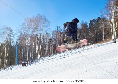 Portrait Of Young Man Performing Snowboarding Stunt Jumping High In Air And Holding Board Backwards