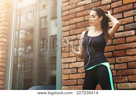 Woman Choose Music To Listen In Her Mobile Phone During Workout In City, Having Rest, Brick Wall Bac