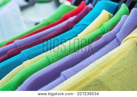 Cotton Polo Shirts Of Various Colors Blue Yellow Red Purple Green White Hanging On Hangers On Rack I