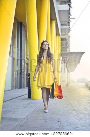 Beautiful woman in yellow dress walking