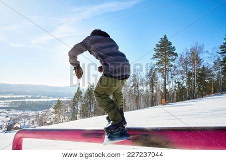 Back View Portrait Of Young Snowboarder Performing Stunt Sliding Down Metal Railing In Sunlight At S