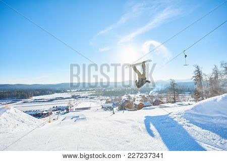 Full Length Action Shot Of Young Man Performing Snowboarding Stunt Backside Flip Jumping In Air In S