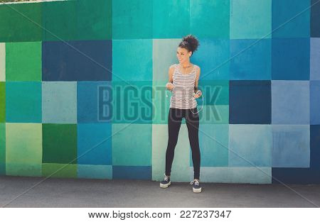 Happy Smiling African-american Woman Posing At Bright Blue Graffiti Wall, While Listening Music, Rel