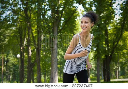 Happy Young Sporty African-american Woman Running In Green Park During Morning Workout, Copy Space