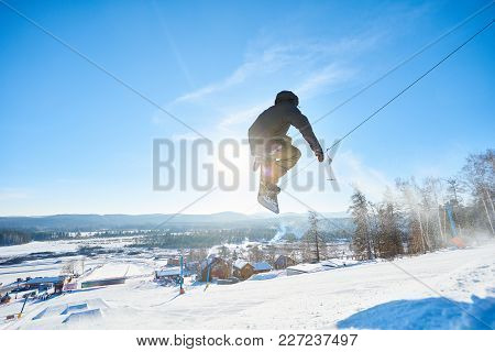 Full Length Action Shot Of Young Man Performing Snowboarding Stunt Jumping High In  Sunlight At Ski