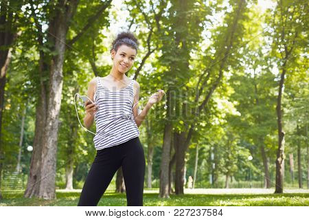 Happy African-american Woman Posing In Sunny Summer Park, While Listening Music, Relaxing From Jog T