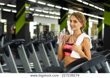 Beautiful Young Sporty Woman Resting After Hard Workout In Gym. Fitness Woman Listening To Music On