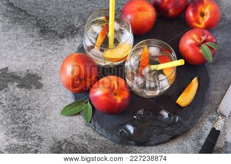 Summer Diet Cold Drink: Detox Pure Water With Nectarine And Ice, Two Glasses On Dark Background. Top