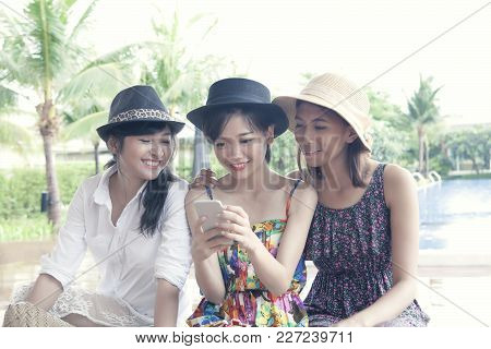 Group Of Young Asian Woman Friend Watching On Smart Phone Screen With Toothy Smiling Face Happiness