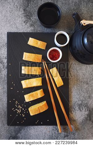 Japanese Omelet Roll Egg Sweet  With Red And Soy Sauces. Top View, Dark Background