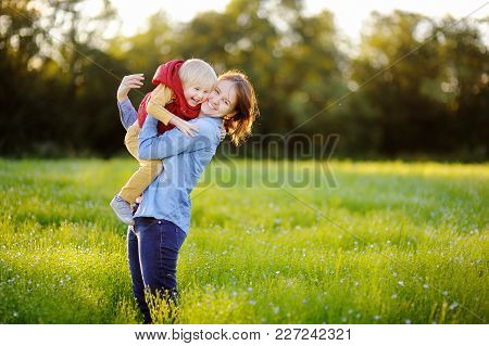 Young Mother Holding Her Little Son During Walk In The Flowers Field. Happy Family Together. Youthfu