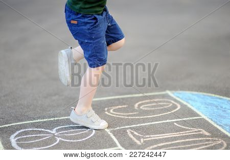 Child Playing Hopscotch Game On Playground Outdoors On A Sunny Day