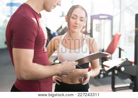 Waist Up Portrait Of Young Woman Signing Contract With Personal Fitness Coach In Modern Gym Club