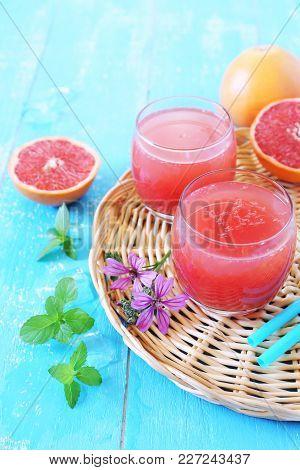 Summer Drink: Grapefruit Pulp Juice In Two Glasses And Grapefruit Halves