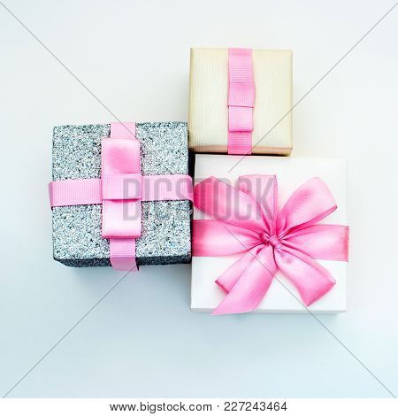 Three Holiday Gift Boxes Tied With Satin Ribbon On Pink Background. Festive Glare Lights. The View F